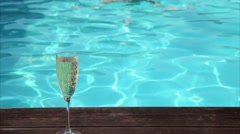 Young happy woman drinks champagne in a swimming pool Stock Footage