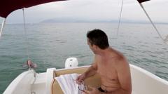 Man in Boat Watching Daughter Swim Stock Footage