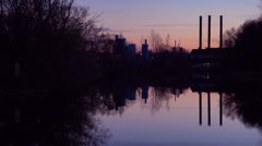 A beautiful sunset over a lake with the smokestacks of industry background. Stock Footage