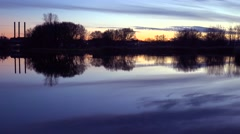 Slow pan across a beautiful sunset over a lake with the smokestacks of industry Stock Footage