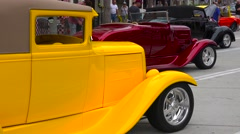 People wander on the streets of a small town looking at classic cars on display. Stock Footage
