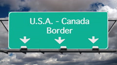 USA Canada Border Crossing Highway Sign with Time Lapse Clouds Stock Footage