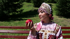 Girl in Russian national dress sniffing a red apple Stock Footage