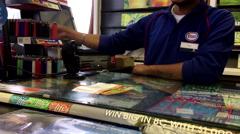 Esso clerk giving customer reciept for buying lottery ticket Stock Footage