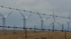 Wind power on Big Island of Hawaii. Rack focus from barbed wire to wind farm Stock Footage