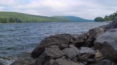 Waves Crashing on Rocks Near Lake During Cloudy Summer Day Stock Footage