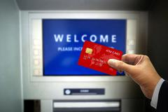 Hand Holding ATM Card at ATM machines Stock Photos