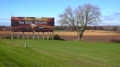 A billboard in the Midwestern countryside implores people to take the Bible Stock Footage