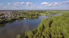 Aerial typical russian countryside landscape village with church on lake shore. - stock footage