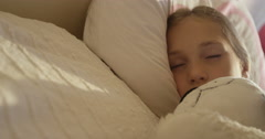 Cute little yawning girl in pajamas lying in a bed under a white blanket Stock Footage
