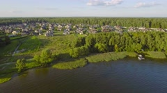 Aerial countryside landscape, fields forest and village with cozy houses on lake - stock footage