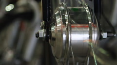 Shiny steel wheel spinning, vehicle production and maintenance business, closeup Stock Footage