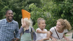 4K Happy mixed race family at outdoor activity center watching a race & cheering Stock Footage