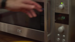 Man hand putting pizza into microwave  Stock Footage