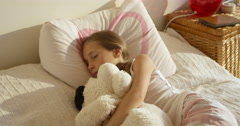 Adorable cute awaking girl in the bed with her toy Stock Footage
