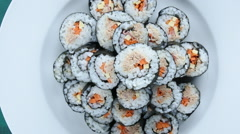 Close up of chopsticks holds sushi maki gunkan roll over a plate Stock Footage
