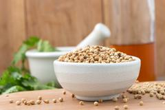 Coriander seeds in a bowl for add Flavor to Your Food on Chopping Wood and Wo Stock Photos
