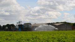 Time lapse water cannon watering crops in field by farm united kingdom Stock Footage