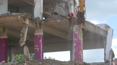 Hydraulic crusher excavator backoe machinery working on demolition area Stock Footage
