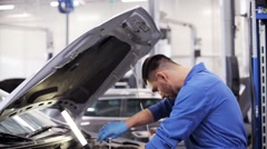 mechanic man with wrench repairing car at workshop - stock footage