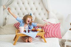 Cute little girl eats and yawn on a bed Stock Photos