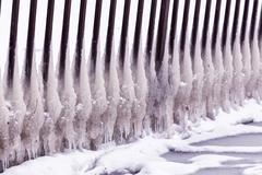 Cold winter day with many icicle on the fence Stock Photos
