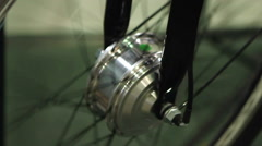 Shiny steel bike wheel rotating at repair shop, active lifestyle, extreme sport Stock Footage