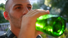Man drinking alcohol beer from bottle outdoors in park in sun back light haze Stock Footage