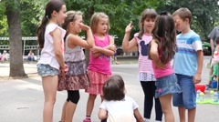 Group of kids play by a childrens playground in a park Stock Footage