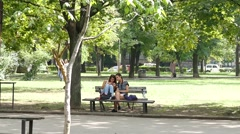 Teenager girls sit on bench in park with smart phone play app chase pokemons Stock Footage