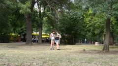 Teenager girls walk in park with tablet and smart phone play app search pokemons Stock Footage