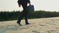 Businessman with case goes away, the frame can be seen only the legs. Goes on - stock footage