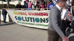 Global warming protestors walk on a city street. Stock Footage
