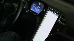 Hand of male driver tapping large touch screen panel in modern electric vehicle Stock Footage