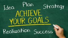 Hand writing on a chalkboard - Achieve your goals Stock Photos