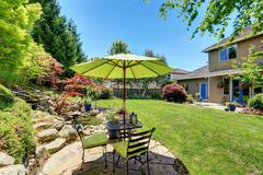 Backyard garden with beautiful landscape. Patio area with umbrella, table and Stock Photos