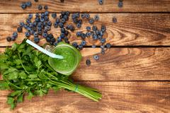 Mug with green smoothie drink and bundle of fresh parsley Stock Photos