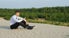Always connected. Young businessman with phone sitting on sand on a background - stock footage