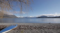 Wide angle shot of lake and canoe - snow capped mountains, shore line. Stock Footage
