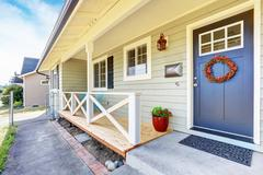 Nice covered porch with wooden floor and railings. Blue entrance door with cu Stock Photos