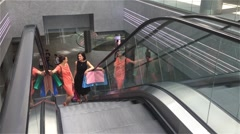 Two girls moving upstairs on escalator in shopping mall, friends are shopping in Stock Footage