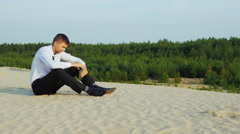Young businessman drinking alcohol from flasks sitting on the sand. Concept - Stock Footage