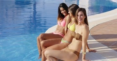 Three sexy young girlfriends relaxing poolside Stock Footage