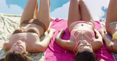 Three sexy girlfriends sunbathing in bikinis Stock Footage