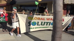 Global warming advocates march holding signs through an urban area. Stock Footage