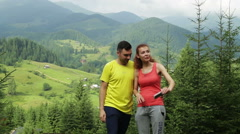 Hiking couple standing on mountain terrain taking a selfie on a sunny day Stock Footage