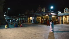 Indian pedestrians spending their evening at the temple compound Stock Footage