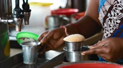 Indian lady pours hot chocolate into filter coffee Stock Footage