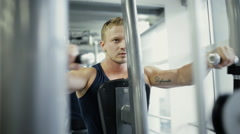 Sportsman lifting weight on training apparatus in gym Stock Footage