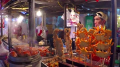 Night Street Food Market Stall with Grilled Crabs and Squids on Sticks. Stock Footage